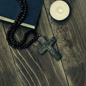 Iron cross with a book and candle — Stock Photo