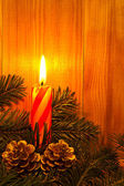 A burning candle among the spruce branches — Stock Photo