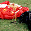 Stock Photo: Red paraglider and his empty bag