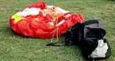 Red paraglider and his empty bag — Stock Photo