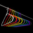 Plastic coat hangers on black background - Stock Photo