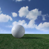 Golf ball on fairway with fluffy clouds skyline — Stock Photo