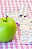Apple and pills — Stock Photo