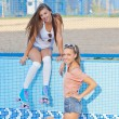 Two beautiful young girls in sunglasses in an empty pool — Stock Photo #15830485