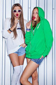 Two beautiful young girls with red lollipops near the wall — Stock Photo
