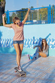 Two beautiful young girls wearing sunglasses in an empty pool — Stock Photo