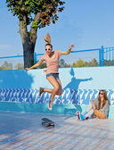 два красивых молодых девушек в солнечных очках в пустой бассейн — Стоковое фото