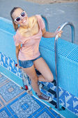A beautiful young girl with a scateboard on the pool ladder — Stock Photo