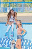 Due belle ragazze giovani in occhiali da sole in una piscina vuota — Foto Stock