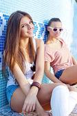 Due belle ragazze giovani sul pavimento di una piscina vuota — Foto Stock