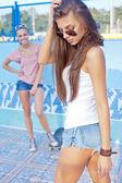 Två vackra unga flickor på golvet i en tom pool — Stockfoto