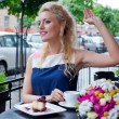 Stock Photo: A beautiful young blond girl in summer dress at the table in pav