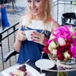 Stock Photo: Beautiful young blond girl in summer dress at table in pav
