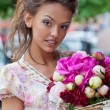 A beautiful young girl in summer dress with a bunch of flowers i — Stock fotografie