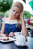 A beautiful young blond girl in summer dress at the table in pav — Stock Photo