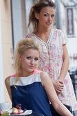 Två vackra unga flickor i sommar outfit luncha på fliken — Stockfoto