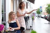 Two beautiful young girls in summer outfit have lunch at the tab — Stock Photo