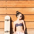 Beautiful gsexy girl with skateboard poses against wooden wall — Stock Photo #34995577