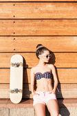 Güzel gsexy kız kaykay ile ahşap duvara teşkil etmektedir — Stok fotoğraf