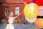 Beautiful lady in retro outfit holding a bunch of balloons — Stock Photo