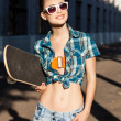 Beautiful lady with skateboard in the city — Stock Photo