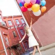 Beautiful lady in retro outfit holding a bunch of balloons — ストック写真