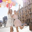 Stock Photo: Two beautiful ladys in retro outfit holding a bunch of balloons