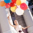 Beautiful lady in retro outfit holding a bunch of balloons — Stok fotoğraf