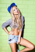 Sexy suntan girl in short jeans shorts against green brick wall — Stock Photo