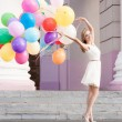 Beautiful lady in retro outfit holding a bunch of balloons — Zdjęcie stockowe