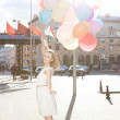 Beautiful lady in retro outfit holding a bunch of balloons — Stock Photo #35750791