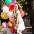 Beautiful lady in retro outfit holding a bunch of balloons — Stock fotografie
