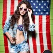 Beautiful sexy long haired girl against american flag — Stockfoto