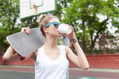 Beautiful sexy lady in white t-shirt with skateboard — Stock Photo