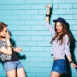 Stock Photo: Young people having fun in front of light blue brick wall