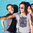 Young people having fun in front of light blue brick wall — Stock Photo