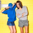 Young people having fun in front of yellow brick wall — Stock Photo