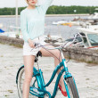 Beautiful girl with city bike at sea pier — Stock Photo