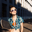 Beautiful lady with skateboard in the city — Stock Photo #44067795