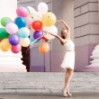 Beautiful lady in retro outfit holding a bunch of balloons on th — Stock Photo