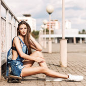 Beautiful lady with long silky hair in denim short overalls — Photo