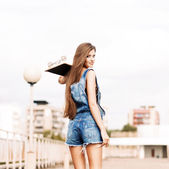 Beautiful lady with long silky hair in denim short overalls — Stock Photo