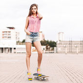 Beautiful lady in short jeans shorts stands on skateboard — Stock Photo