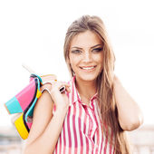 Beautiful woman in sleeveless striped top holding bright high he — Stock Photo