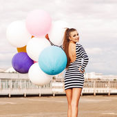 Beautiful lady in short black and white striped dress holds bunc — Stock Photo