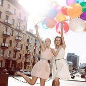 Iki güzel bayanın retro kıyafeti bir sürü balon holding — Stok fotoğraf