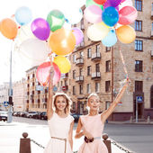 Two beautiful ladys in retro outfit holding a bunch of balloons — Stock Photo