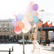 Beautiful lady in retro outfit holding a bunch of balloons on th — Stock Photo #44070729