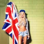 Sexy suntan girl in short jeans shorts against green brick wall — Stock Photo #44071017