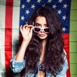 Beautiful sexy long haired girl against american flag — Stock Photo